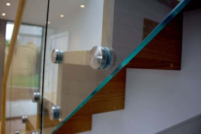 close up of point fixed glass on timber staircase