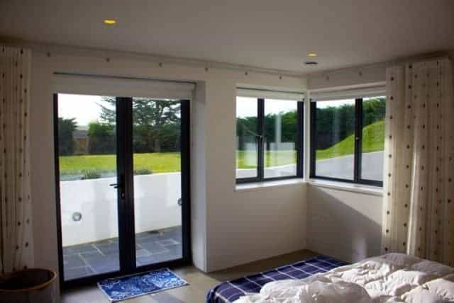 bedroom with black aluminium windows and patio door